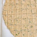 garlic and herb sourdough discard crackers on parchment before baking