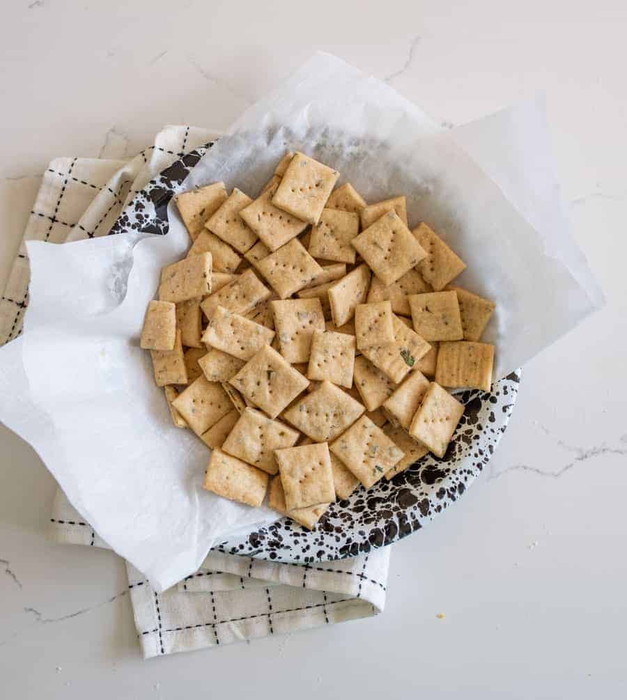 herb and garlic sourdough crackers on parchment in black and white bowl on white countertop