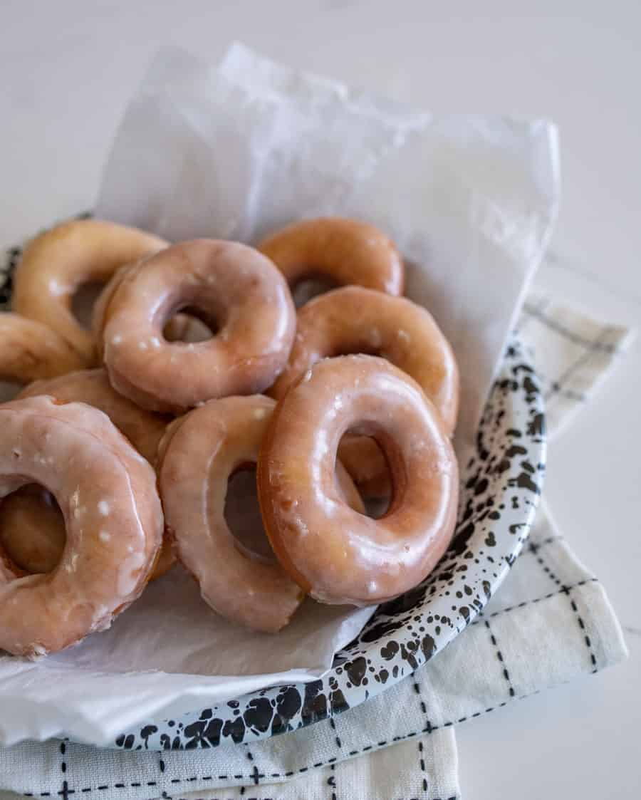 glazed donuts resting in a speckled serving dish