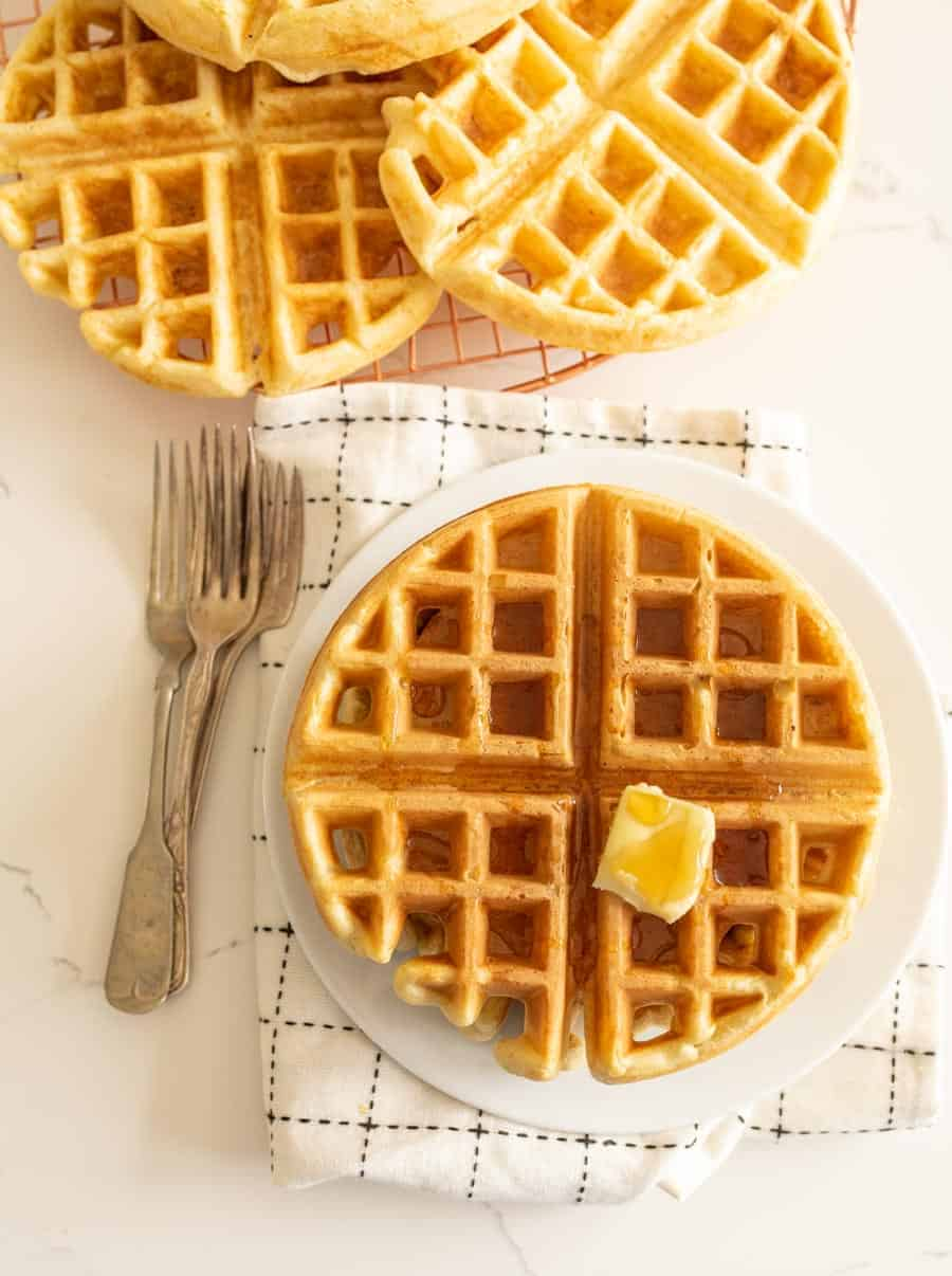 sourdough waffle on round white plate with pat of butter on white towel with forks