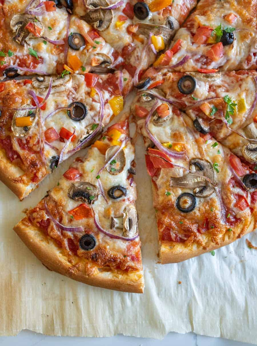 closeup of homemade veggie pizza on parchment