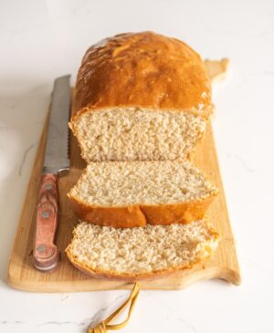 loaf of sliced bread on cutting board with knife