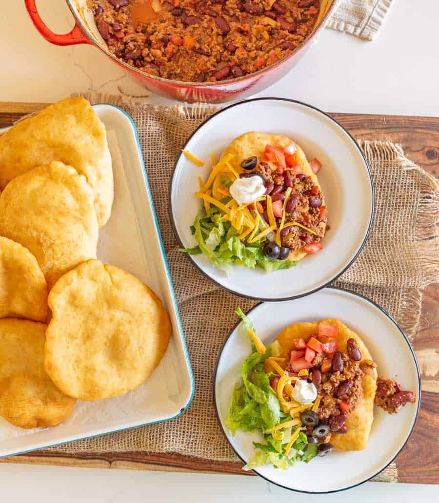 fry bread on plates made into Navajo tacos with lots of toppings