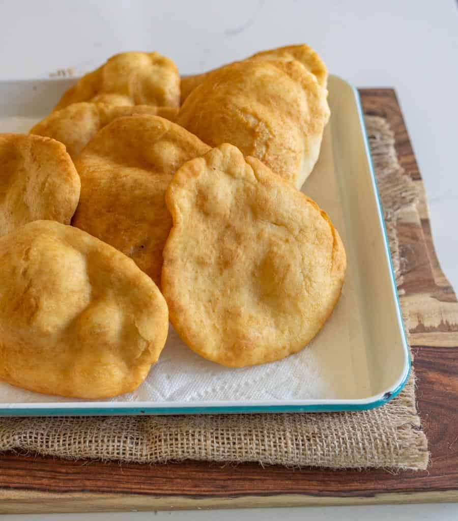 cooked fry bread on a rimmed sheet cooling