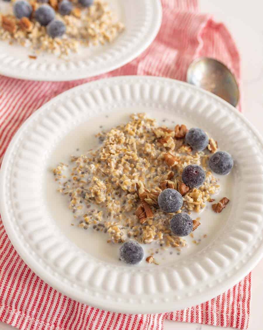 two white bowls of steel cut oats with fruit on red and white striped towel