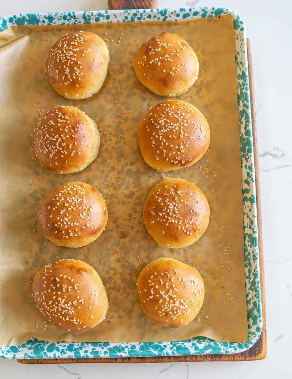 sourdough burger buns on parchment paper after baking