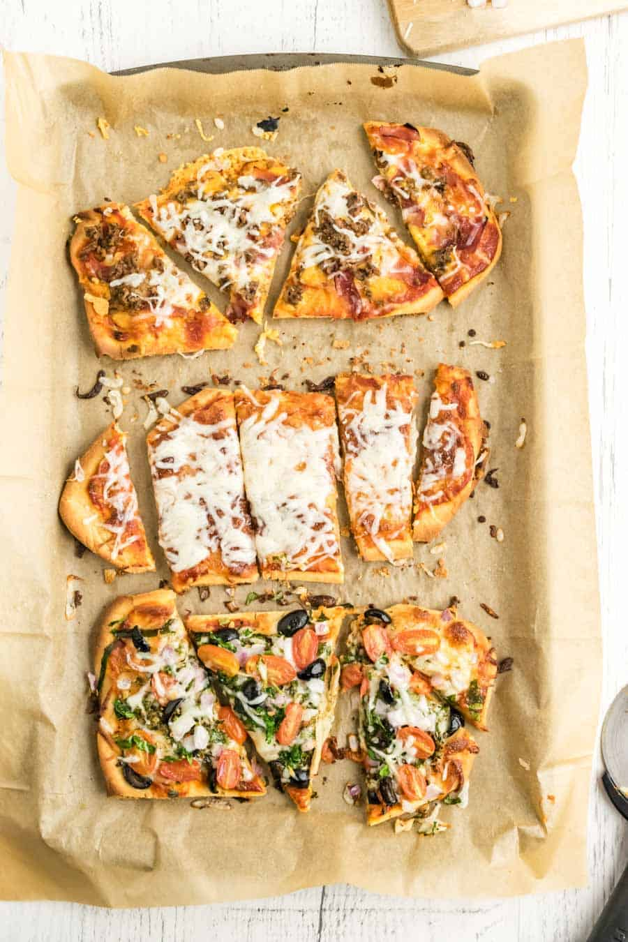 3 kinds of flatbread pizza baked and sliced on a baking sheet