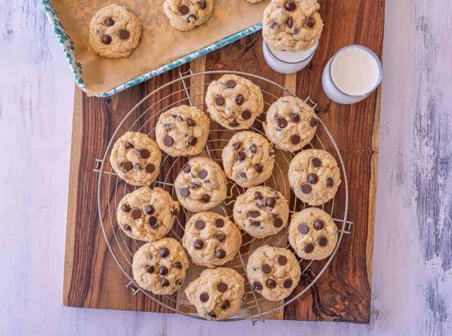 baked sourdough chocolate chip cookies on a cooling rack with glassed of milk next to them
