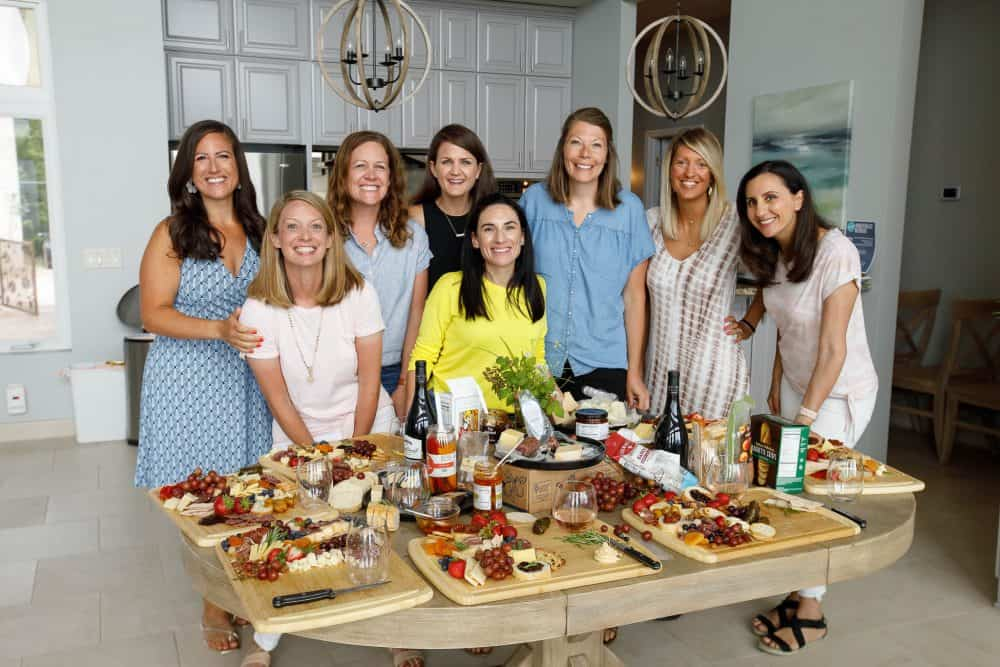 women smiling around table of cheese