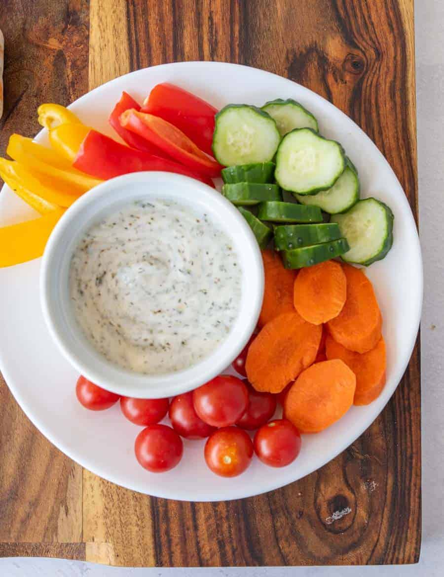 plate of colorful veggies with dip in a bowl
