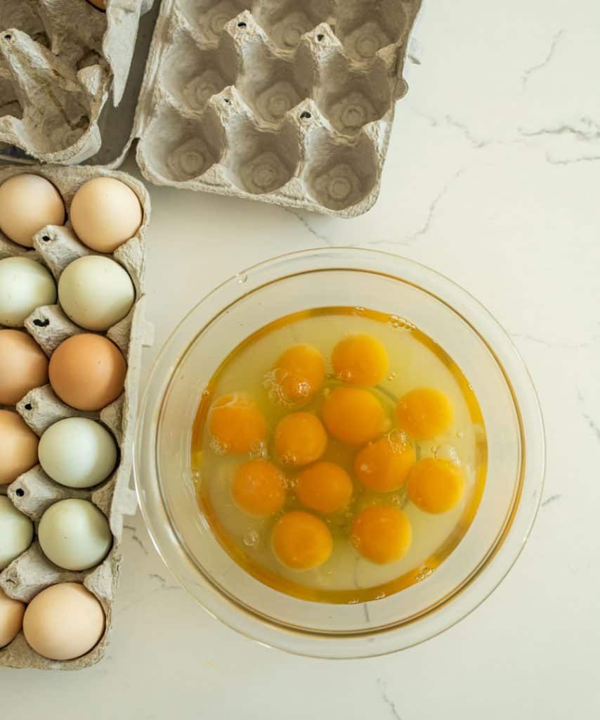 cracked raw eggs in a glass bowl