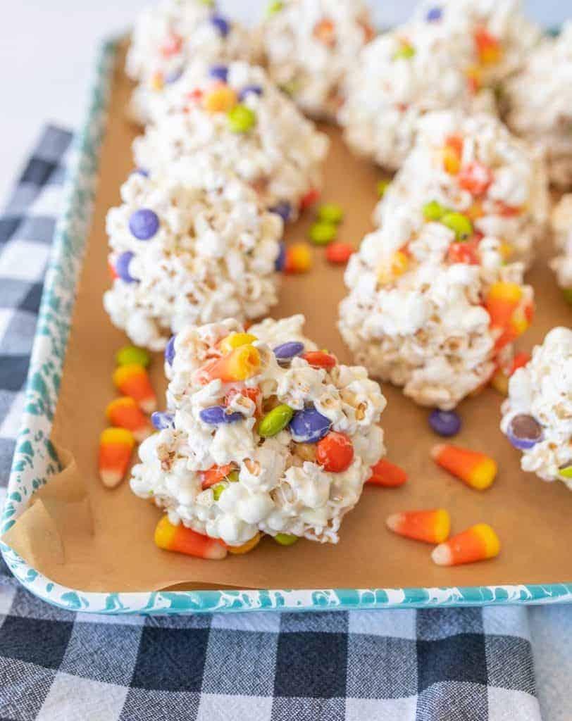 halloween popcorn balls with candy corn on enamel baking sheet