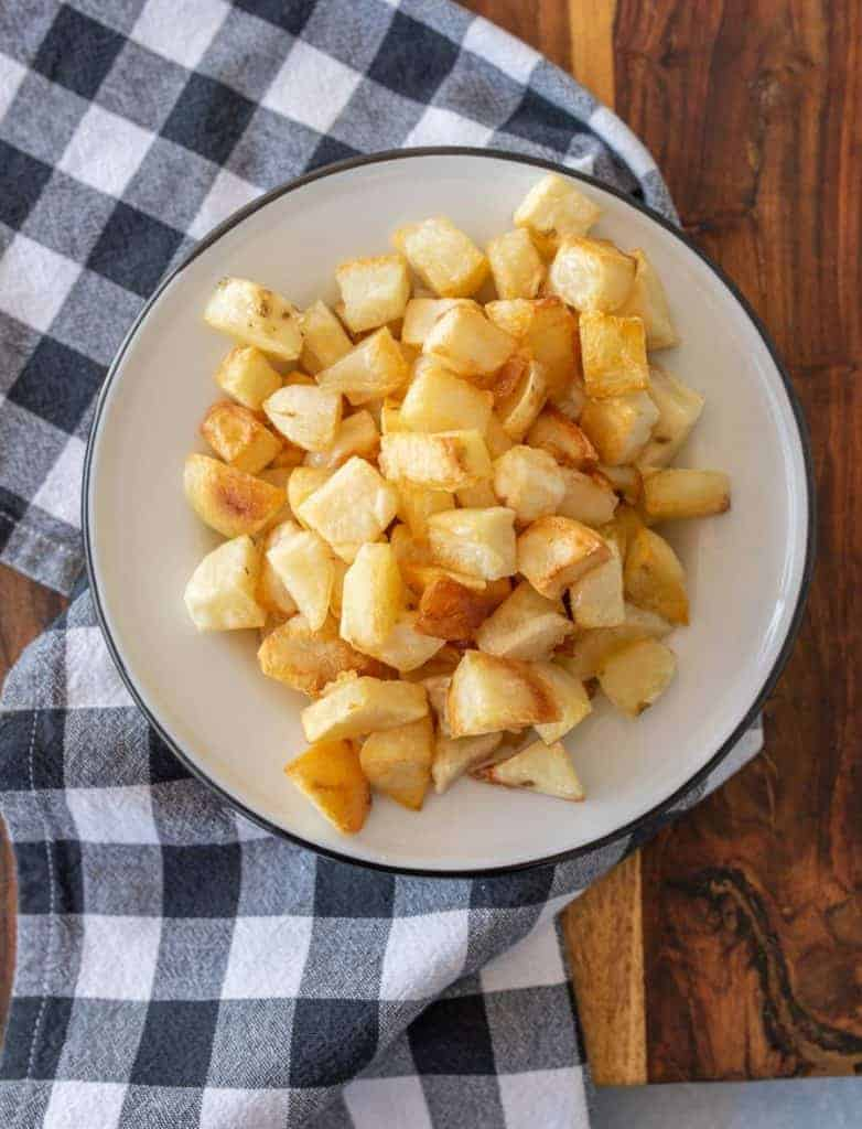 crispy oven roasted potato cubes on enamel plate on gingham tablecloth
