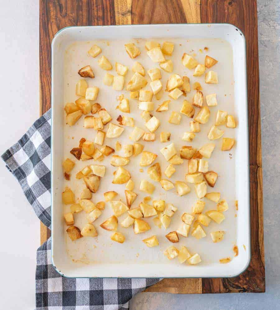 crispy oven roasted potato cubes on enamel baking sheet on gingham tablecloth on wood cutting board