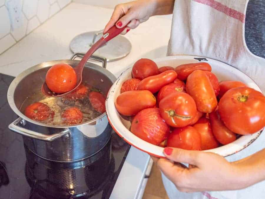 spoon removing blanched tomato from water bath
