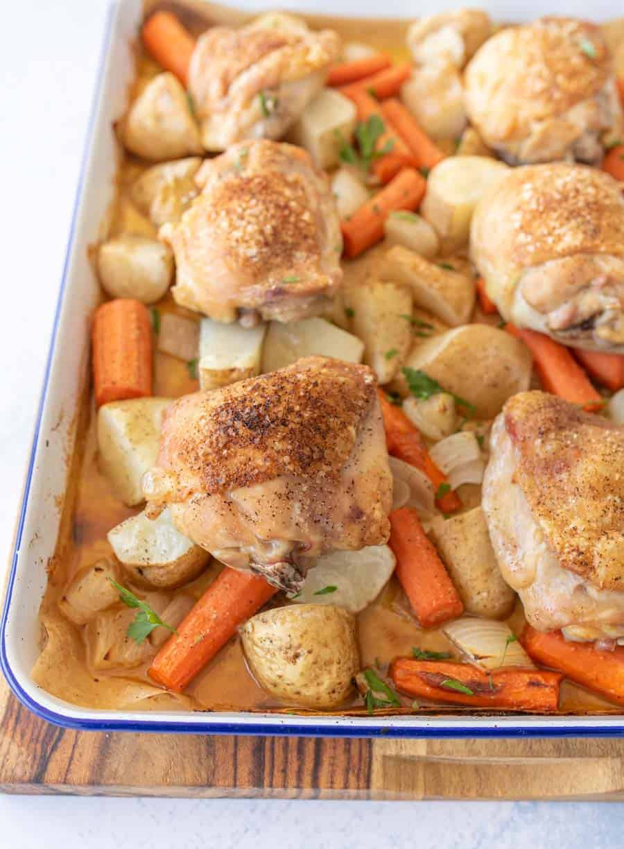 oven roasted chicken thighs, carrots, potatoes, and onions on enamel baking sheet with garnish