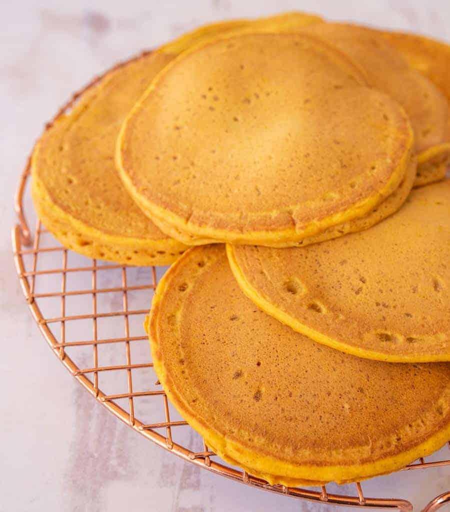 6 golden orange pancakes on a cooling rack