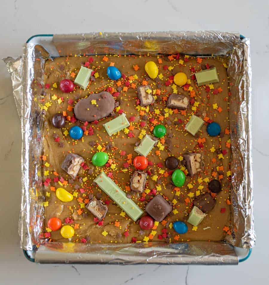 unbaked cookies bars with assorted candy on top