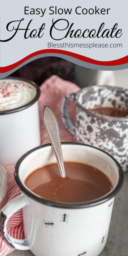 """Picture of a white mug of hot chocolate with a spoon in it and a few mugs in the background and the words """"easy slow cooker hot chocolate"""" written at the top"""