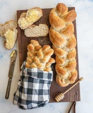 4 loaves of bread bread on a dark wood cutting board