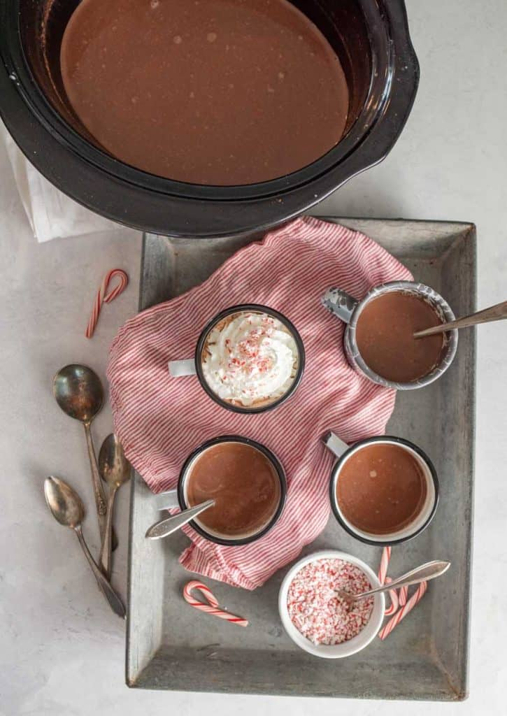 top view of tray of mugs filled with crock pot hot chocolate next to the crock pot of hot chocolate