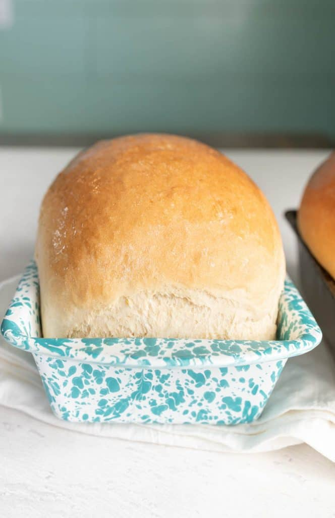 loaf of white sandwich bread in a white and blue speckled loaf pan.