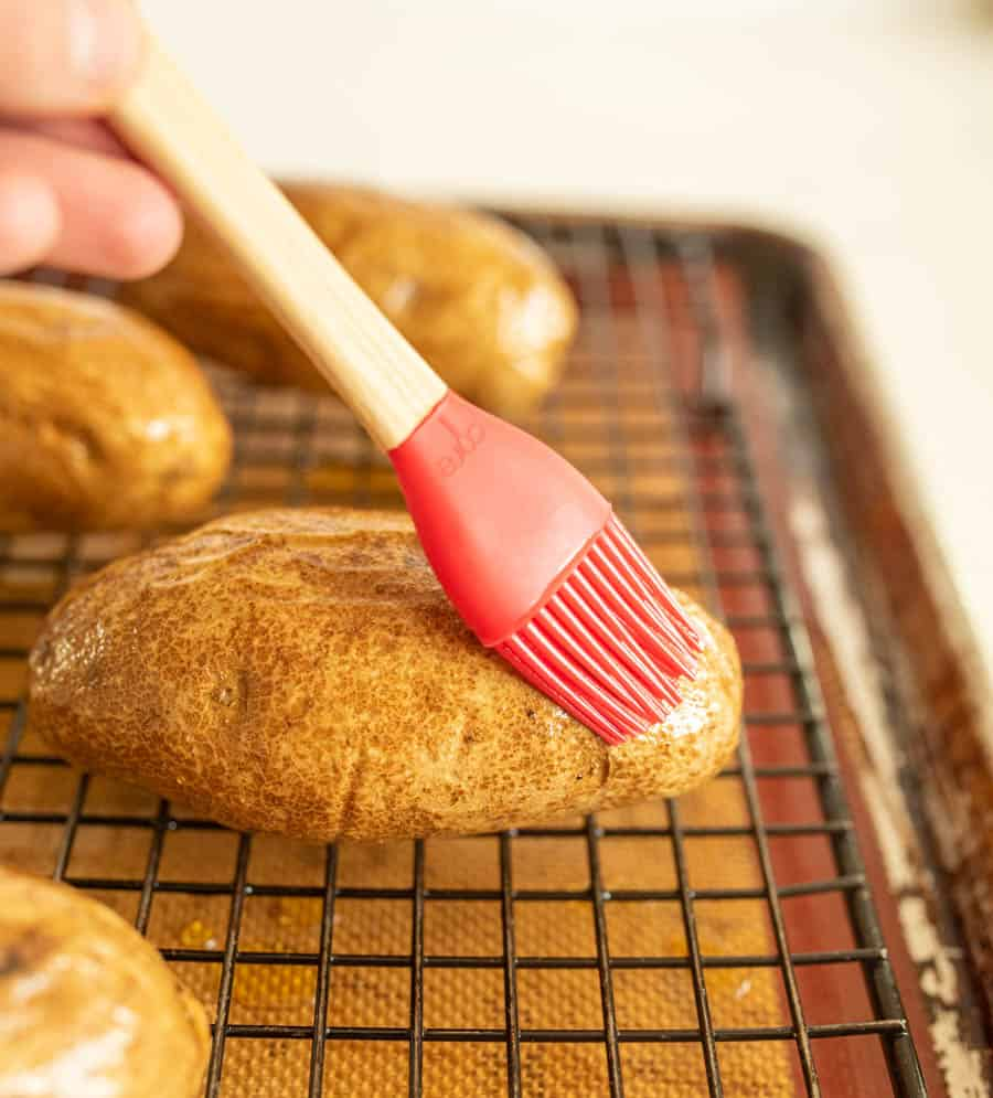 Potato being brushed with oil by pastry brush