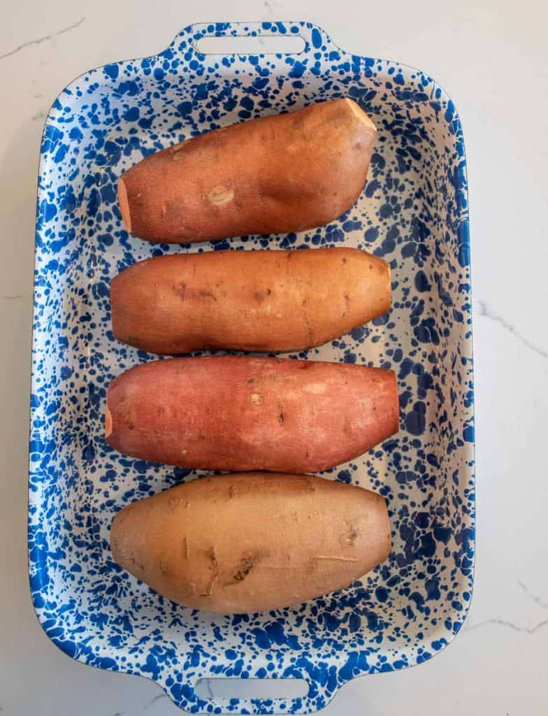 four sweet potatoes in a baking dish