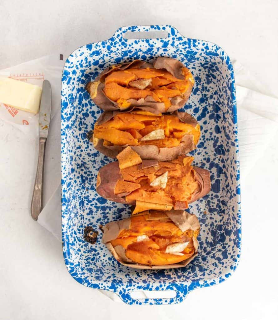 top view of baked sweet potatoes in a white and blue speckled baking dish
