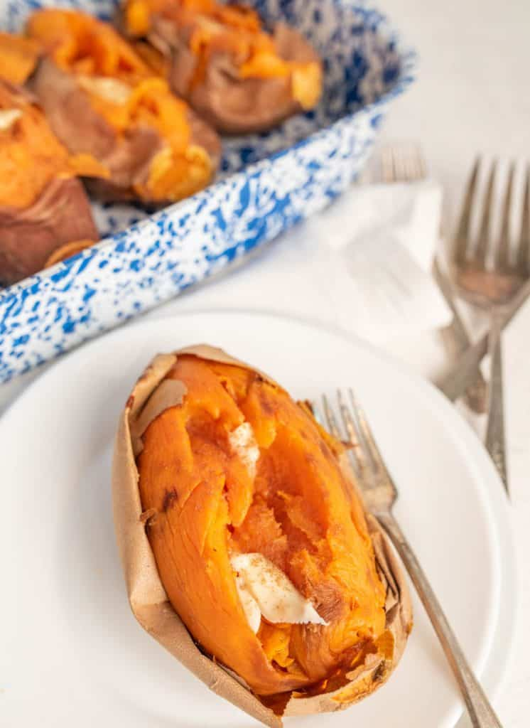 baked sweet potato with butter on it on a white plate with a fork