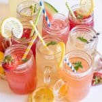 Glass mugs filled with different types of lemonade with straws in them