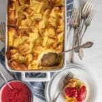 top view of French toast breakfast casserole dish with a portion of it on a plate and a bowl of raspberry sauce