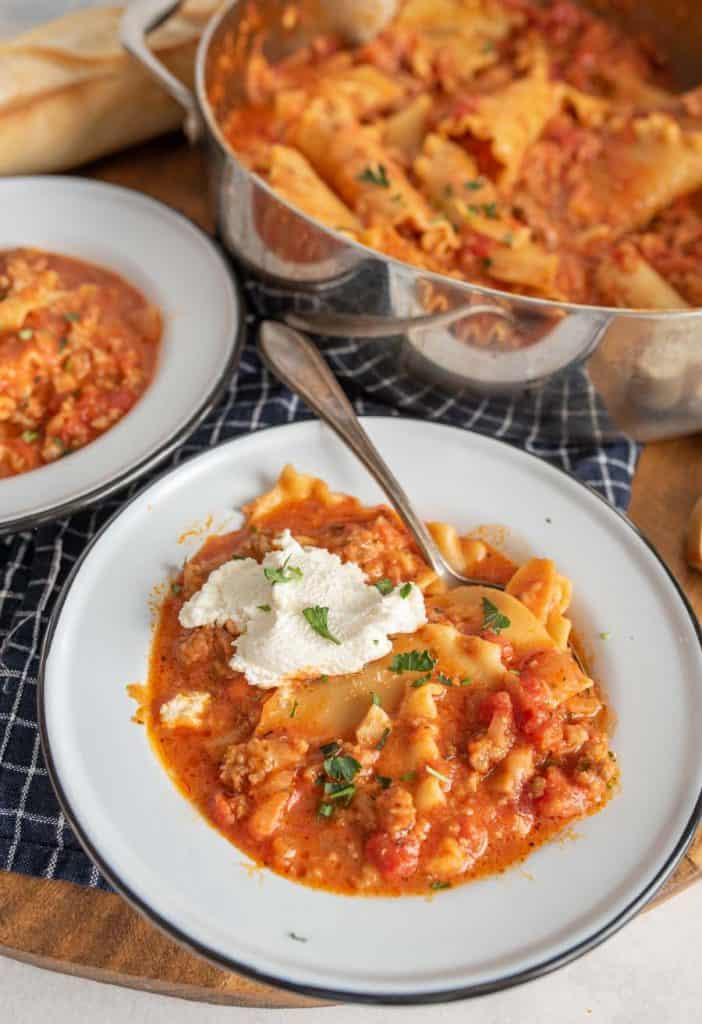 lasagna soup with a dollop of ricotta on top and parsley