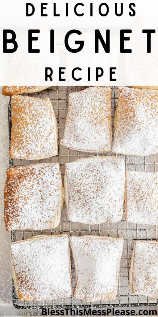 """top view of a cooling rack of beignets covered in powdered sugar and the words """"delicious beignet recipe"""" written at the top"""