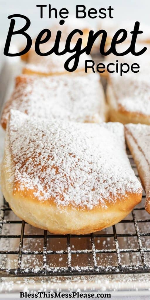 """close up of a beignets on a cooling rack with the words """"the best beignet recipe"""" written at the top"""