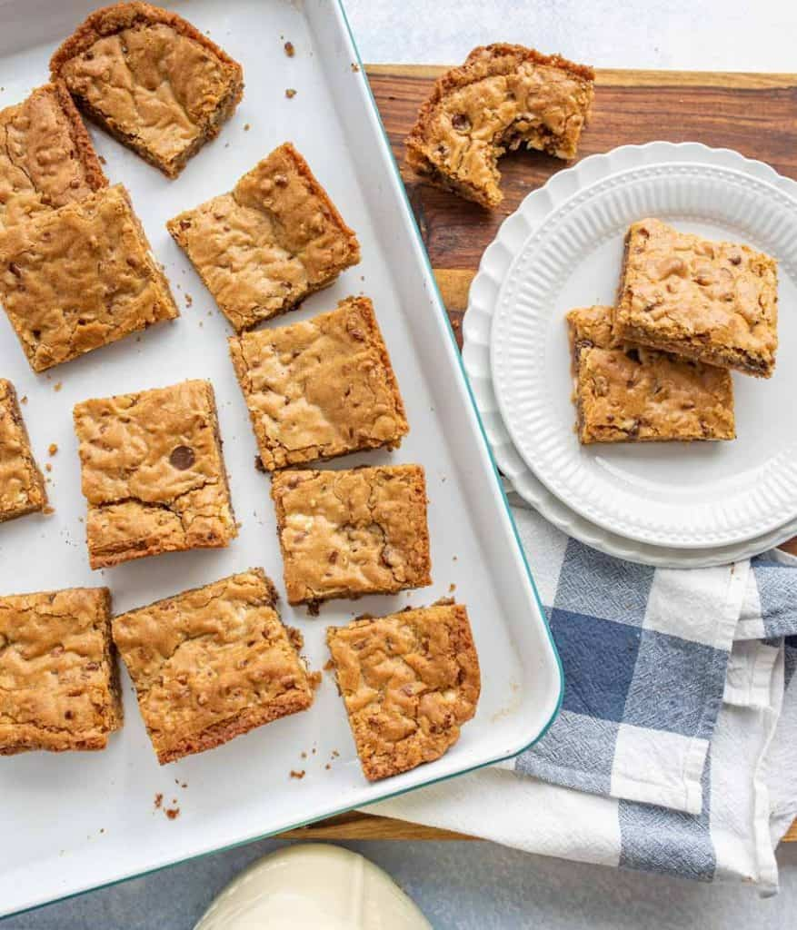 top view of a pan of blondies with a plate of blondies next to it