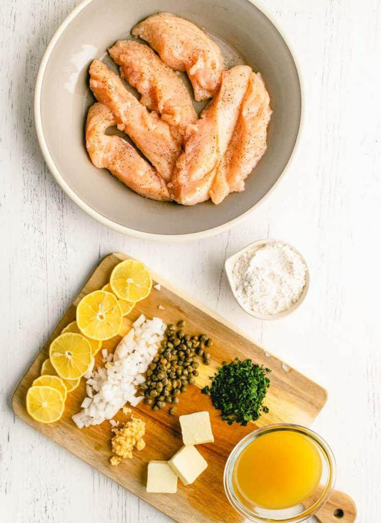 top view of a bowl of chicken and a cutting board with the ingredients for chicken picatta on it