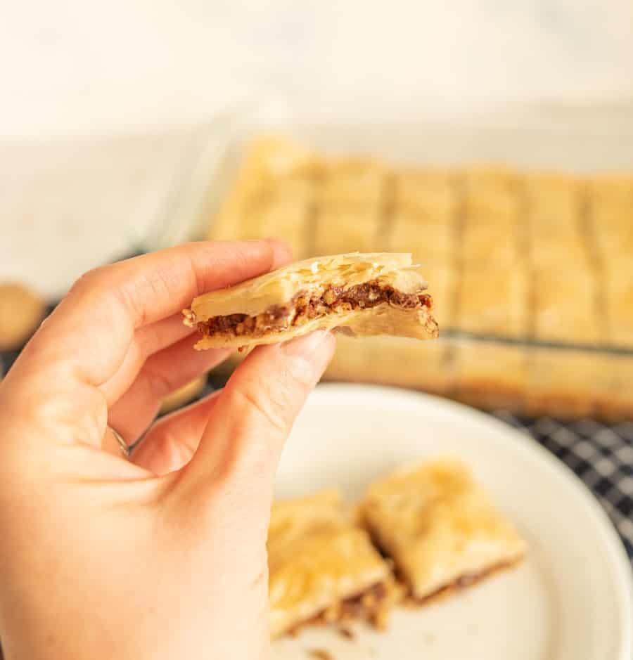 close up of a hand holding a piece of baklava