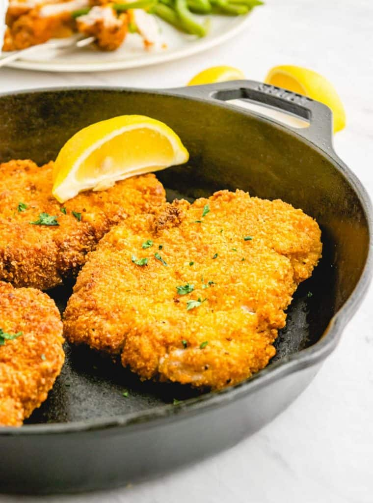 close up picture of crispy fried pork chops in a cast iron skillet with a lemon slice