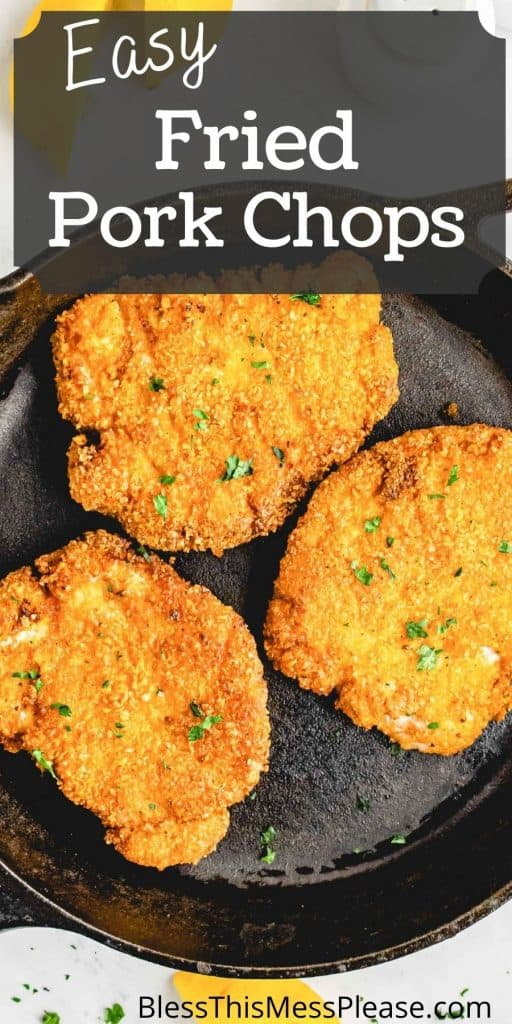 """top view of three crispy fried pork chops in a cast iron skillet with the words """"easy fried pork chops"""" written at the top"""