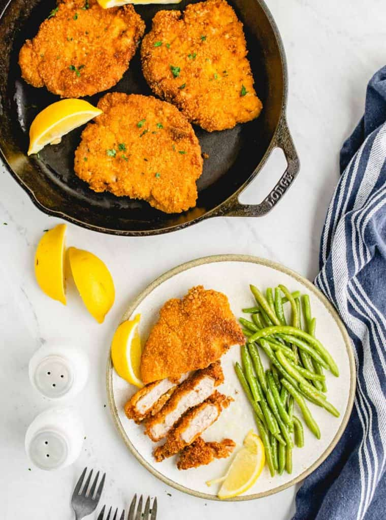 top view of cirspy fried pork chops in a cast iron skillet next to a plate of sliced pork chop and green beans