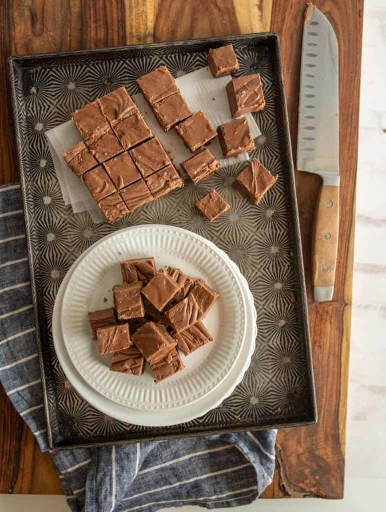 top view of chocolate fudge squares on a plate with fudge squares on a pan and a knife
