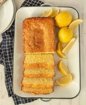 top view of lemon pound cake sliced up on a tray with lemons next to it