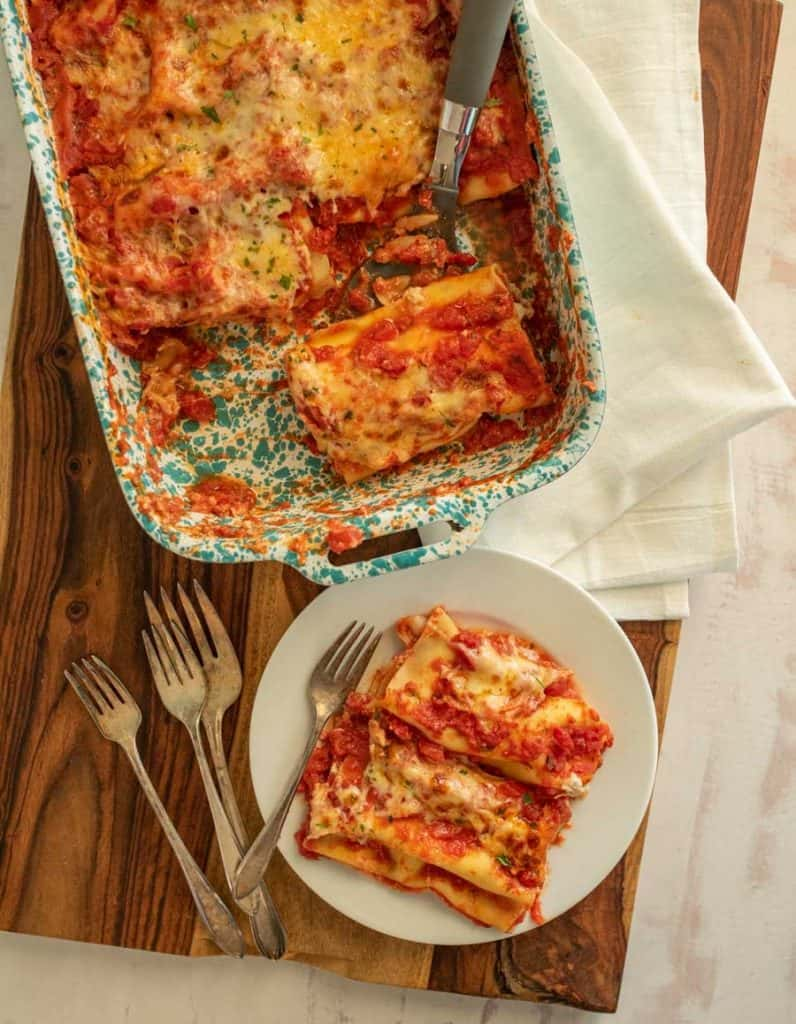 top view of a plate of manicotti and forks next to a pan of manicotti