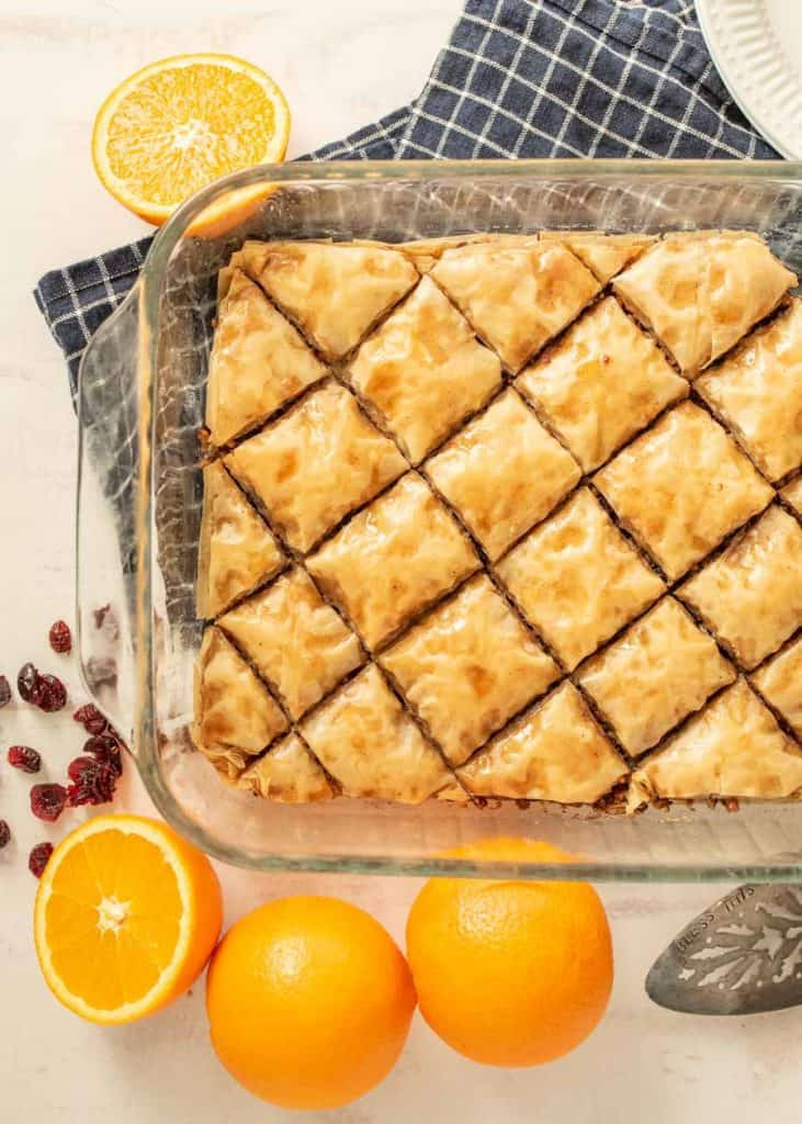 top view of baklava in a pan with oranges and cranberries around the dish