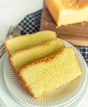 slices of pound cake on a plate with pound cake on a cutting board in the background