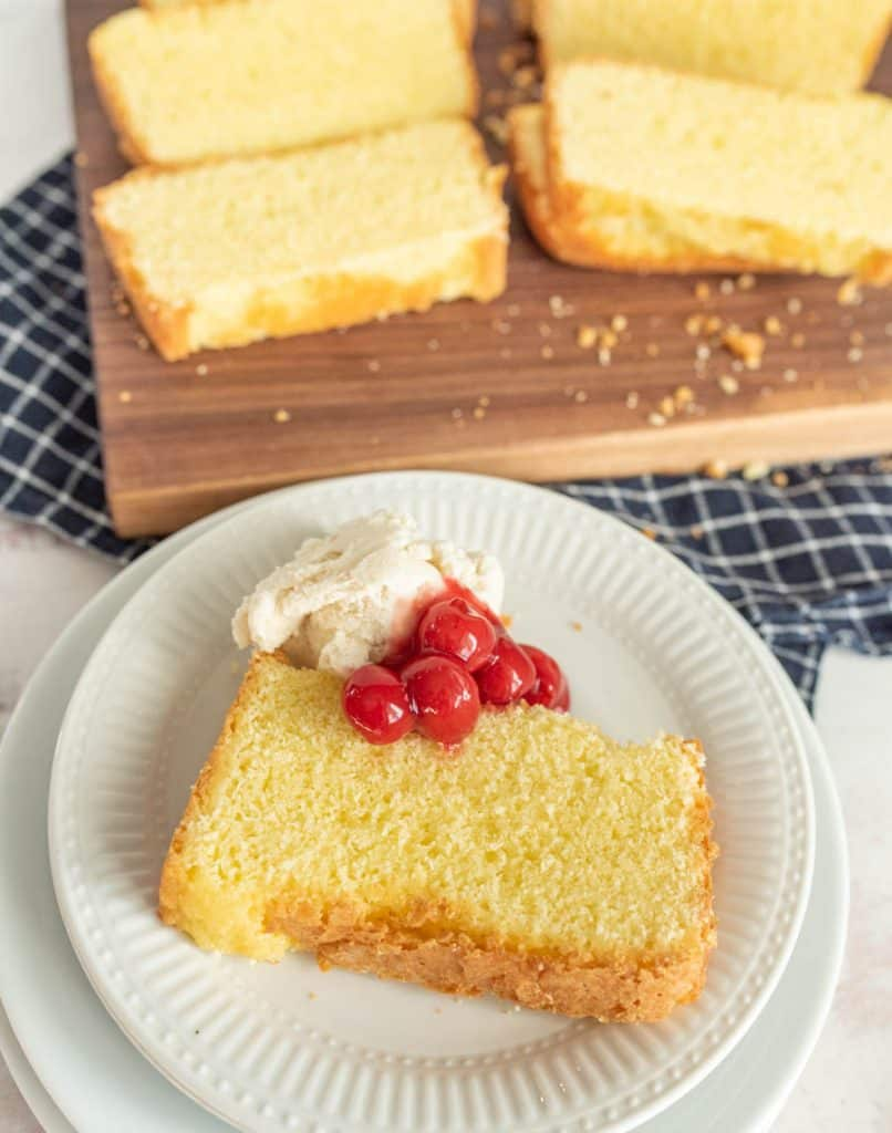 plate of pound cake with ice cream and cherry topping and a cutting board with slices of pound cake in the background