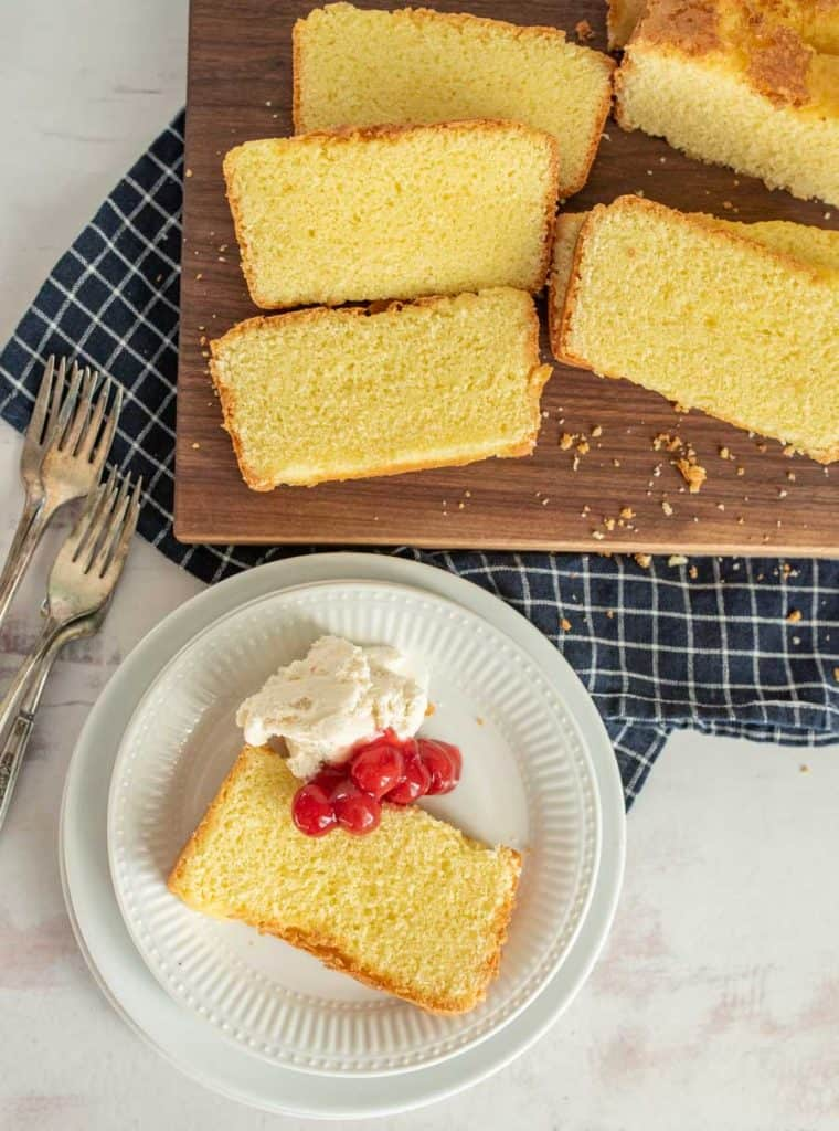 top view of a slice of pound cake with ice cream and cherry topping and a cutting board of slices of pound cake
