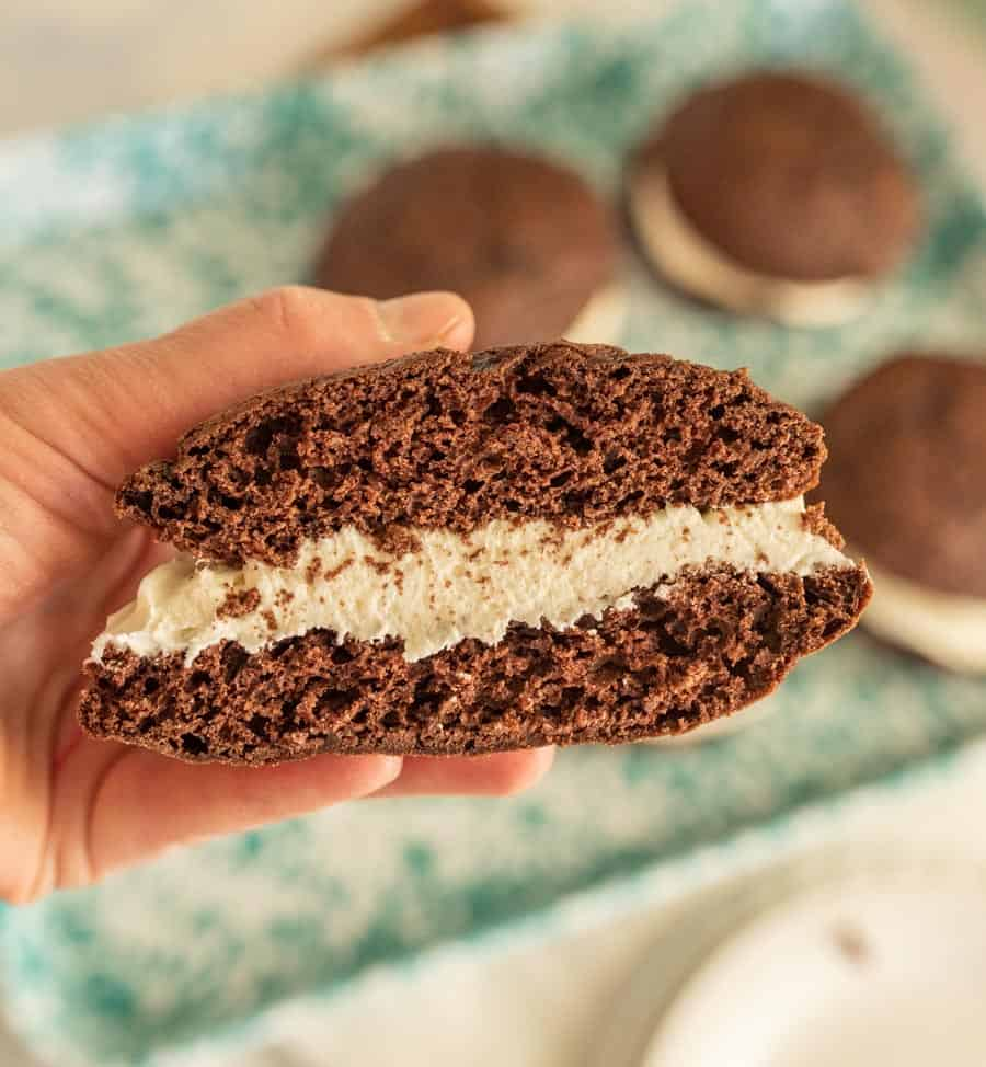 close up of a hand holding a whoopie pie cut in half
