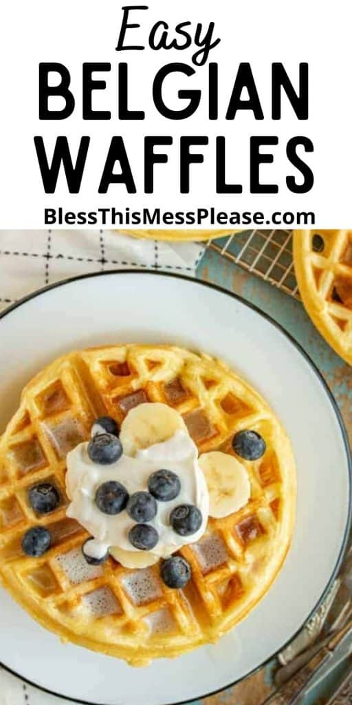 """Top view of a waffle on a plate, topped with blueberries, banana slices, and whipped cream, with the words """"easy Belgian waffles"""" written at the top"""